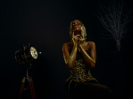 platinum hair: Surreal creative portrait of sexy african american model with glossy gold wig and makeup posing to the camera in black studio background. Fashion Vogue concept.