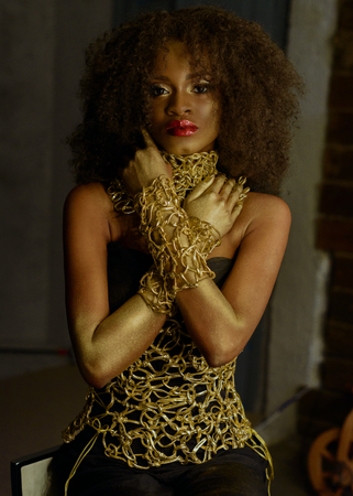 bodypaint: Luxurious portrait of sexy african american female model with glossy golden makeup posing to the camera. Bronze bodypaint, studio background.