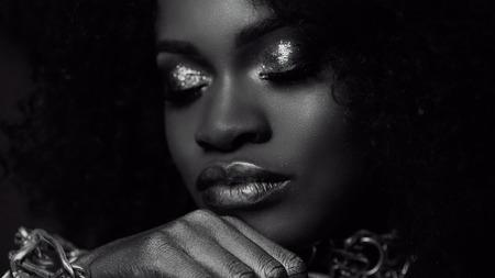 Surréaliste portrait en gros plan noir et blanc de jeune mannequin afro-américaine avec maquillage brillant or. Art du visage. Concept de mode. Banque d'images - 59092121