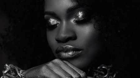 Surreal black and white close-up portrait of young african american female model with gold glossy makeup. Face art. Fashion concept.