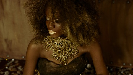 bodypaint: Surreal creative portrait of sexy african american female model with glossy golden makeup posing to the camera on the textured studio background. Wild fashion concept.