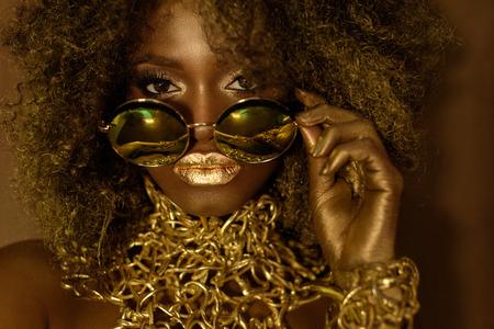 Primer plano de modelo afroamericana de oro mágico mujeres en gafas de sol enormes brillo con maquillaje brillante, peinado de oro brillante y labios rojos grandes que presentan en el fondo del estudio.