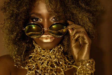 maquillaje fantasia: Primer plano de modelo afroamericana de oro mágico mujeres en gafas de sol enormes brillo con maquillaje brillante, peinado de oro brillante y labios rojos grandes que presentan en el fondo del estudio.