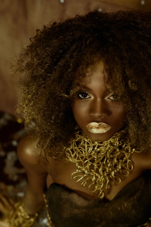 Surreal portrait of sexy african american female model with glossy golden makeup posing to the camera on the studio background. Wild fashion concept. 免版税图像