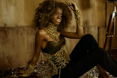 화려한 아프리카 계 미국인 여성 모델 광택 황금 메이크업 질감 된 스튜디오 배경에 카메라와 함께 포즈. 스톡 콘텐츠 - 59018732