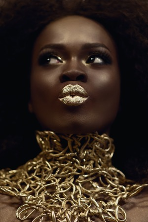 Close-up surreal portrait of majestic african american female model with gold glossy makeup. Fashion concept.