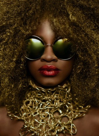 Close-up portrait of magic golden african american female model in massive sunglasses with bright glitter makeup, glossy hairstyle and big red lips. Studio shoot.