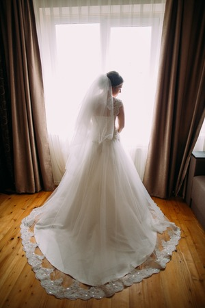 Beautiful bride with long veil standing against window lights.