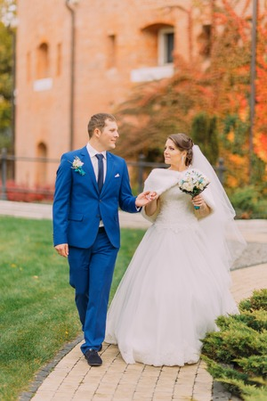 newly married couple: Newly married couple strolling in sunny park at alley. Loving room is gently holding hand of his elegant bride. Stock Photo