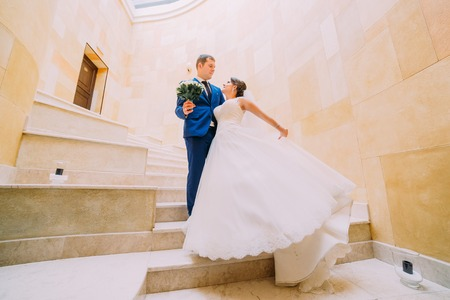 sexual relations: Romantic wedding couple on marble stairs with sandstone walls at background. Low angle view.