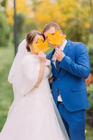 a newly married couple: Newly married couple posing outdoors. Happy and playful young people hiding their faces behind yellow autumn leaves.