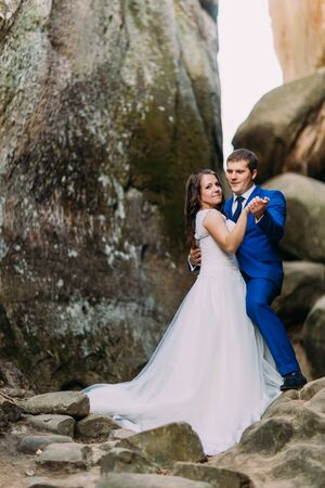 cleft: Young and beautiful bride with her elegant groom dancing in weathered rock cleft.