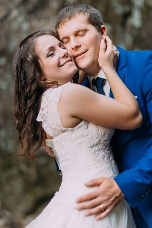 exalted: Closeup portrait of happy groom hugging with his bride. Rough blurry background.