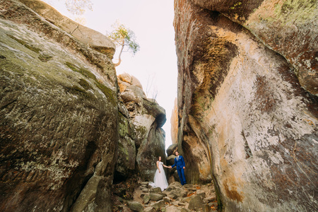 cleft: Young newlywed couple posing in weathered rock cleft holding hands together.