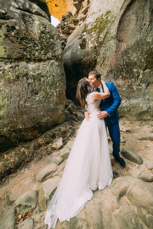 cleft: Young and romantic newlywed couple kissing in weathered rock cleft. Stock Photo
