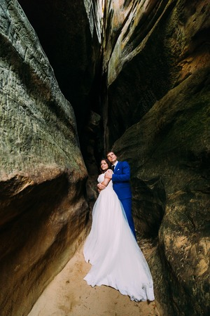 cleft: Young and romantic bride with her loving groom posing in darkened weathered rock cleft. Stock Photo