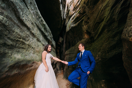 cleft: Handsome groom holding hand of his new wife while both posing in weathered rock cleft. Stock Photo