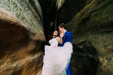 cleft: Young romantic bride in white wedding dress with long tail and her loving groom posing at darkened rock cleft.