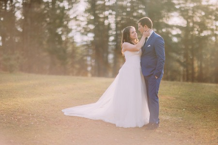 washed out: Romantic wedding couple outdoors. Bride going to kiss her groom. Warm washed out matte style.