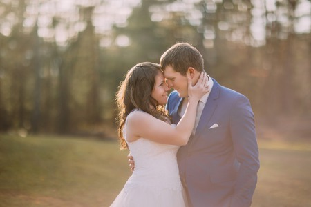 washed out: Romantic wedding couple outdoors. Happy bride going to kiss her groom. Warm washed out matte style.