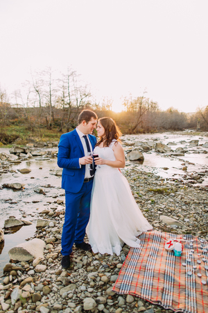 picknick: Romantic young newlywed couple drinking wine on rocky pebble river bank with forest hills and stream as background.