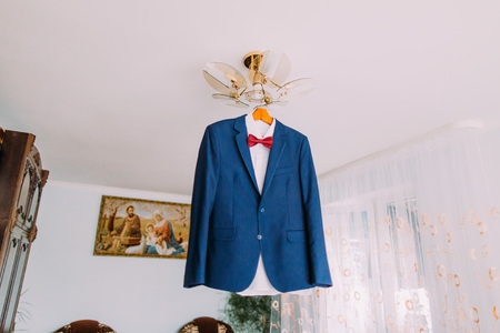 luster: Excellent expensive blue suit with red bow-tie hanging on luster in the interior of brigtht hotel room.
