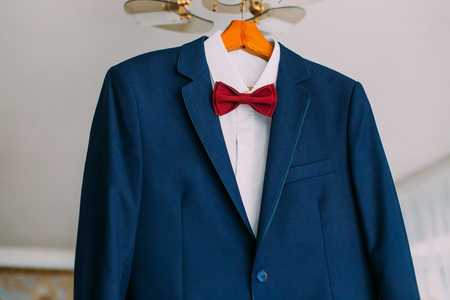 luster: Close-up of excellent expensive blue suit with red bow-tie hanging on luster in the brigtht hotel room interior.