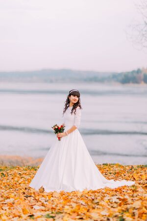 innocent: Beautiful innocent thoughtful bride in gorgeous white dress holding wedding bouquet while stands on fallen leaves at riverside. Stock Photo