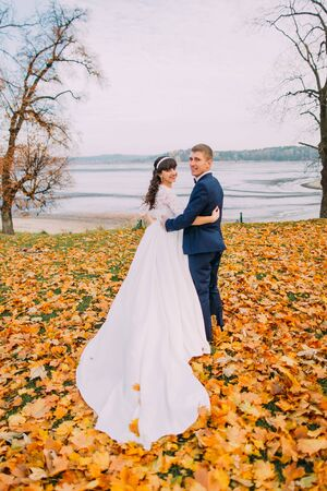newly married couple: Happy young newly married couple posing on autumn lakeshore full of orange leaves.
