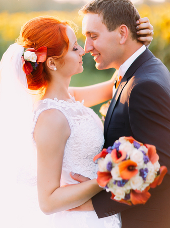 lovingly: Portrait of bright happy redhair bride with unusual appearance and handsome groom lovingly look at each other and embracing in the sunny sunflower field.
