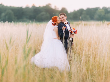 lovingly: Wedding couple in love enjoy a moment of happiness and lovingly look at each other on wheat field. Handsome young man with beautiful redhair girl posing outdoor, enjoying marriage day together.