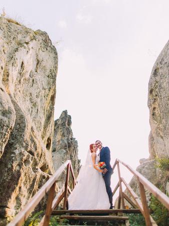 couple lit: Happy young wedding couple posing on the wooden bridge in Carpathian mountains.