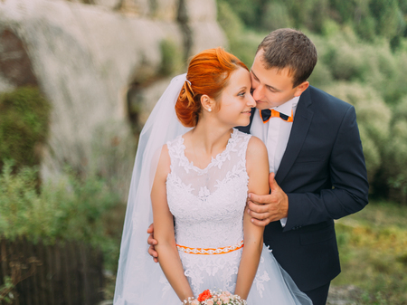 against the flow: Young redhair bride turned to the groom on the background of rocky Carpathian mountains. Stock Photo