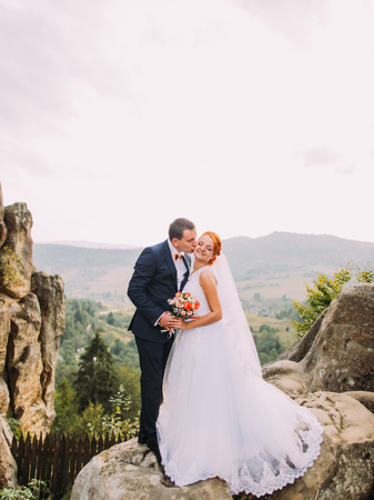 against the flow: Young redhair bride and happy handsome groom softly kissing on the background of rocky Carpathian mountains.