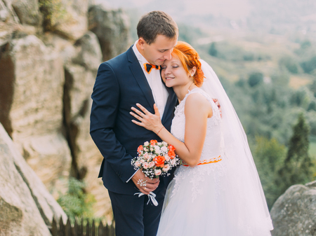 against the flow: Young redhair bride and happy handsome groom softly embracing on the background of rocky Carpathian mountains. Stock Photo