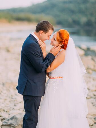 lovingly: Attractive young wedding couple lovingly look at each other  the shore of a mountain river with stones. Stock Photo