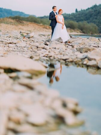 lovingly: Attractive young wedding couple lovingly look at each other. Shore of a mountain river with stones on background.