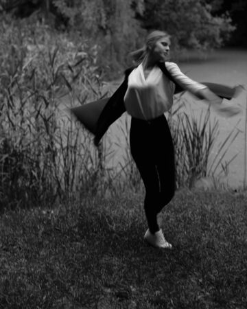 whirling: Charming young girl in casual clothes dancing and whirling in green park, black and white.