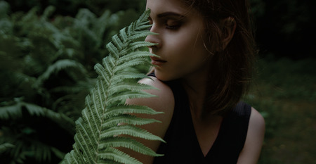Beau visage de jeune femme avec la peau fraîche de santé posant sur la nature avec des feuilles vertes .. Banque d'images