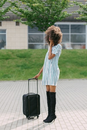 jackboots: Full body portrait of a traveling African American woman wearing short dress and jackboots with suitcase and mobile phone. Stock Photo