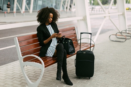 Beautiful african american woman with suitcase using smartphone while sitting on bench near airport Standard-Bild