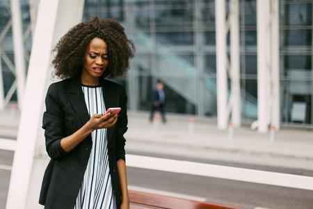 Inquiet jeune femme d'affaires afro-américain parlant au téléphone, bâtiment moderne en arrière-plan. Banque d'images - 59945357