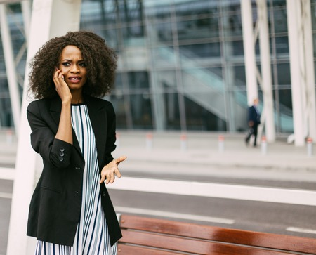 Worried young African American businesswoman talking on phone, modern building as background.