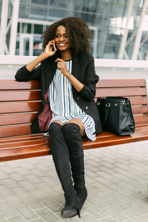 jackboots: Happy African American woman in dress and jackboots using cellphone sitting on bench while waiting for flight.