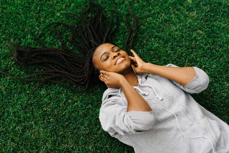 woman laying down: Close up portrait of a beautiful and dreamy African American woman laying down on healthy green grass, relaxing with her eyes closed, smiling outdoors. Stock Photo
