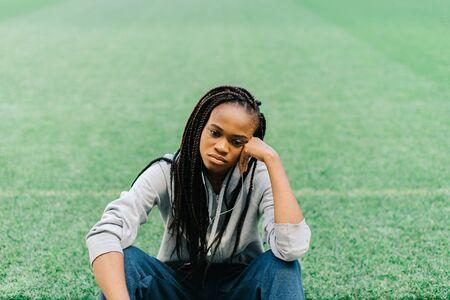 머리에 손으로 앉아 스포티 한 아프리카 계 미국인 여자 경기장에서 푸른 잔디에 대 한 실망 느낌. 스톡 콘텐츠 - 59943717