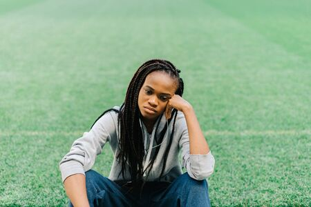 dreariness: Sporty african american woman sitting down with hand on head and feeling disappointed against green grass at stadium.