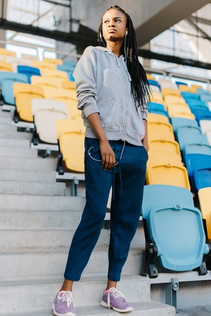Full-length of young african american woman standing in an amongst the rows of empty blue and yellow seats in a stadium. Stock Photo