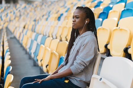 Side view of young african american girl sitting on an empty sports tribune with headphones.