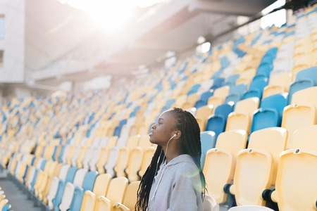 Many blue and yellow plastic chairs and a lone african american girl with headphones on stadium. Stock Photo